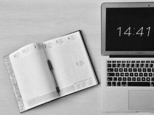 Imagem de uma agenda e um notebook com o relógio aparecendo, para simbolizar o conteúdo sobre horas extras do trabalho