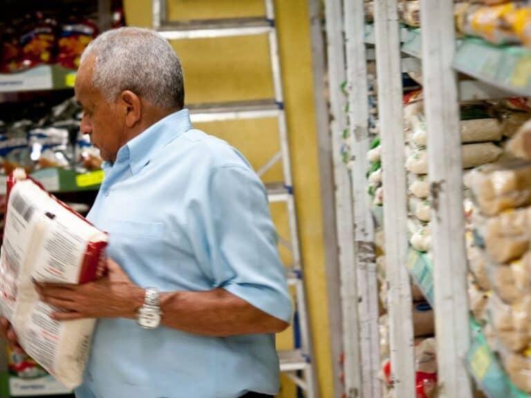 Homem segurando um arroz, exemplo de alimento que puxou a inflação de novembro para cima.
