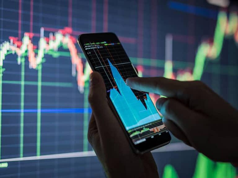 pessoa acessando celular com gráfico, representando apostas de investimentos