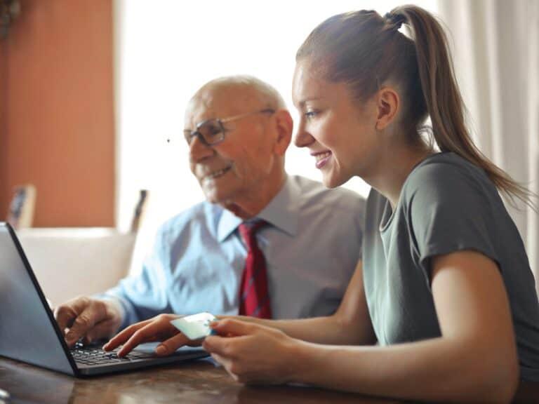 jovem e idoso acessando computador, representando investimentos arriscados