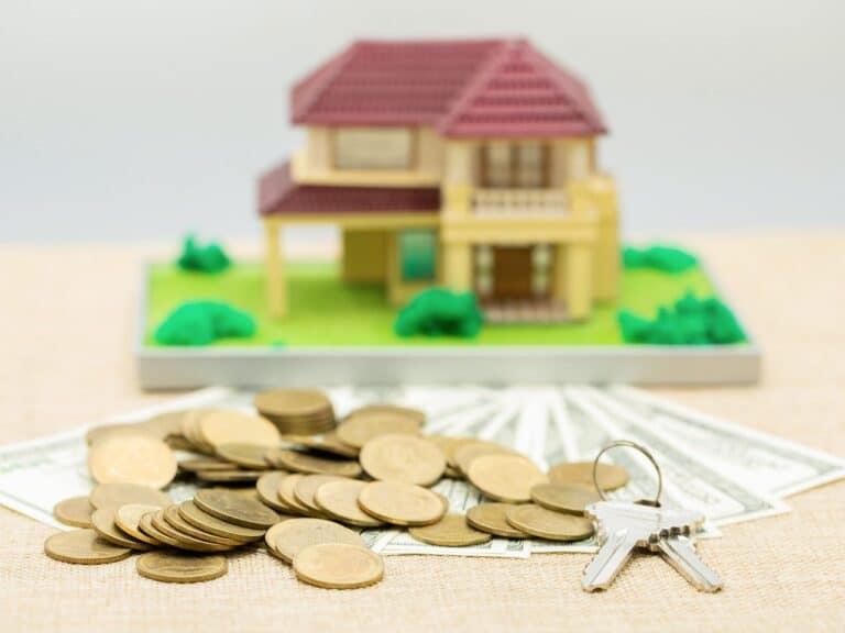 miniatura de casa e moedas, representando investir em imóveis em 2021