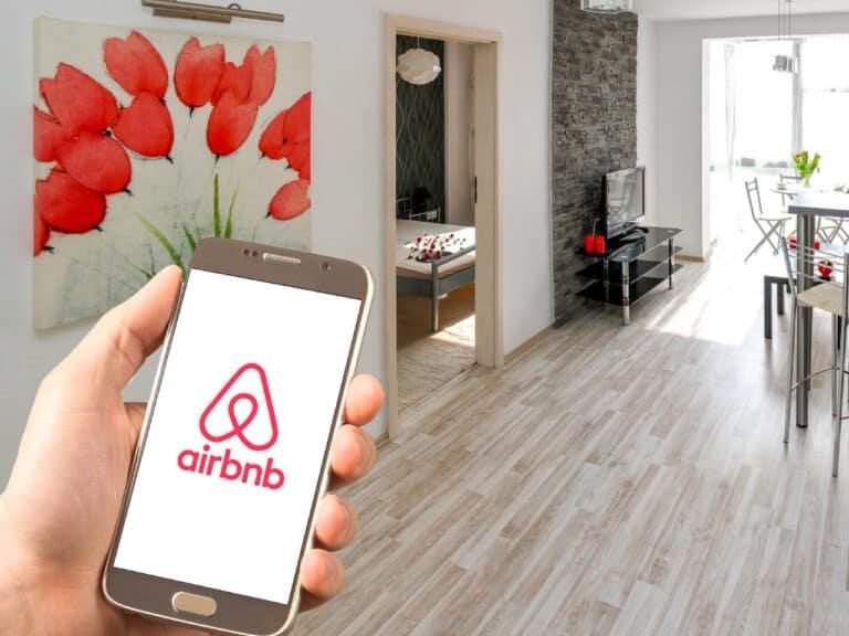mão segurando celular com logo do airbnb, que abre hoje ipo