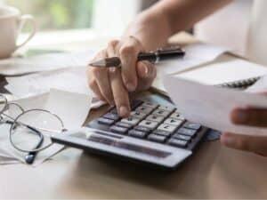 Imagem de uma pessoa usando um papel, calculadora e uma caneta para fazer contas e anotações. Usamos a imagem para representar o conteúdo sobre juros compostos