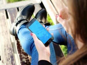 mulher segurando smartphone em banco de praça representando microcrédito e Casa Verde e Amarela pelo Caixa Tem