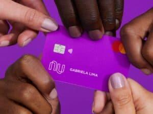 Imagem de várias pessoas segurando um cartão Nubank para ilustrar o conteúdo sobre o Nubank Rewards