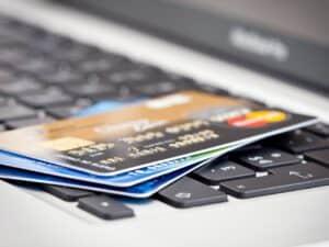 Imagem de vários cartões de crédito em cima de um laptop para representar nosso conteúdo que explica o que é o CVV do cartão