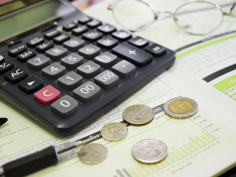 caneta, moedas e calculadora em cima de livro de matemática representando poupança tem perda de quase 2%