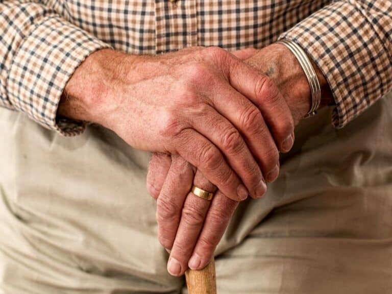 close em mãos de idoso segurando bengala representando prazo de concessão da aposentadoria