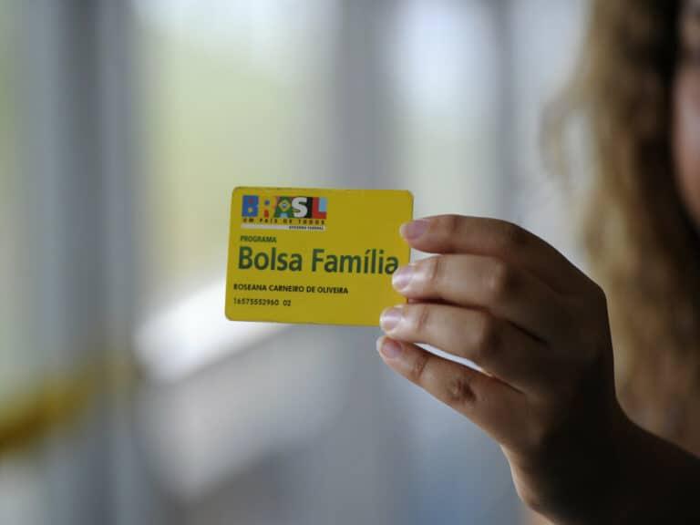 dedos da mão de uma pessoa aparecem segurando um cartão do Bolsa Família