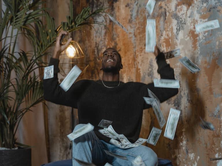 pessoa jogando cédulas de dinheiro para cima, representando prêmio da mega da virada