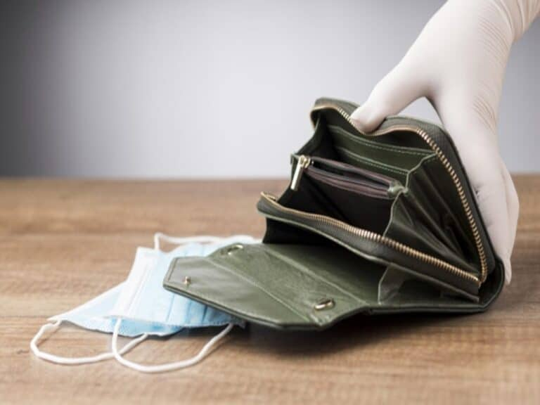 Pessoa segura a carteira de dinheiro em cima de máscaras, representando receber 13º antecipado