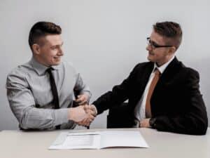 homens de gravata trocando aperto de mãos, representando retornar ao mercado de trabalho