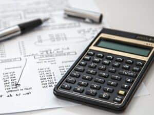 Imagem de uma calculadora, caneta e documentos, simbolizando o conteúdo sobre a calculadora de salário anual