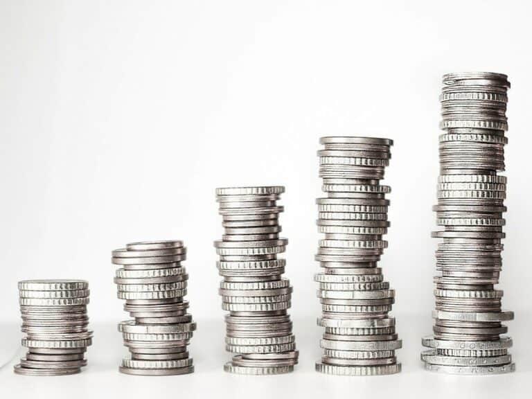 5 pilhas de moedas, uma mais alta do que a outra, em formato ascendente, representando salário mínimo 2021