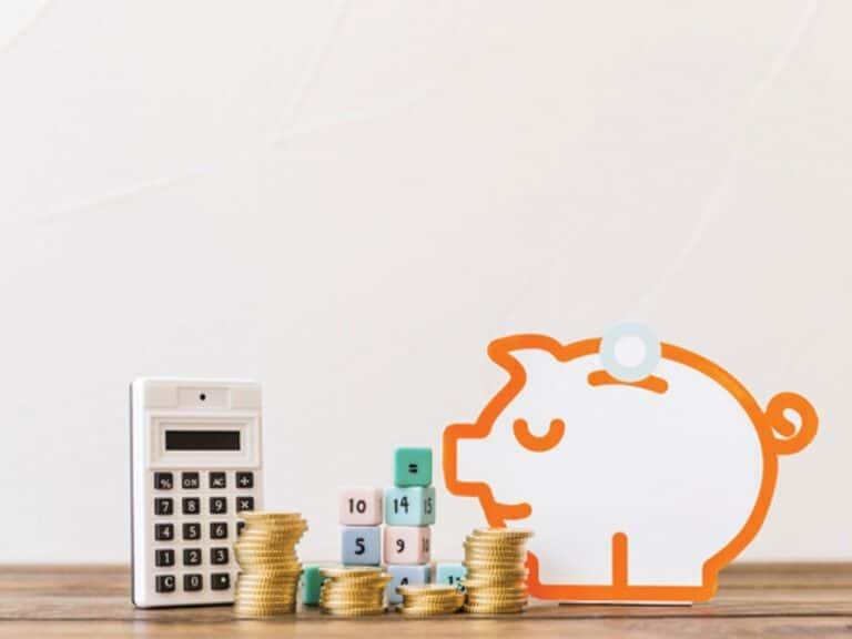 calculadora ao lado de moedas, dados e um porquinho, representando taxa selic em 2021