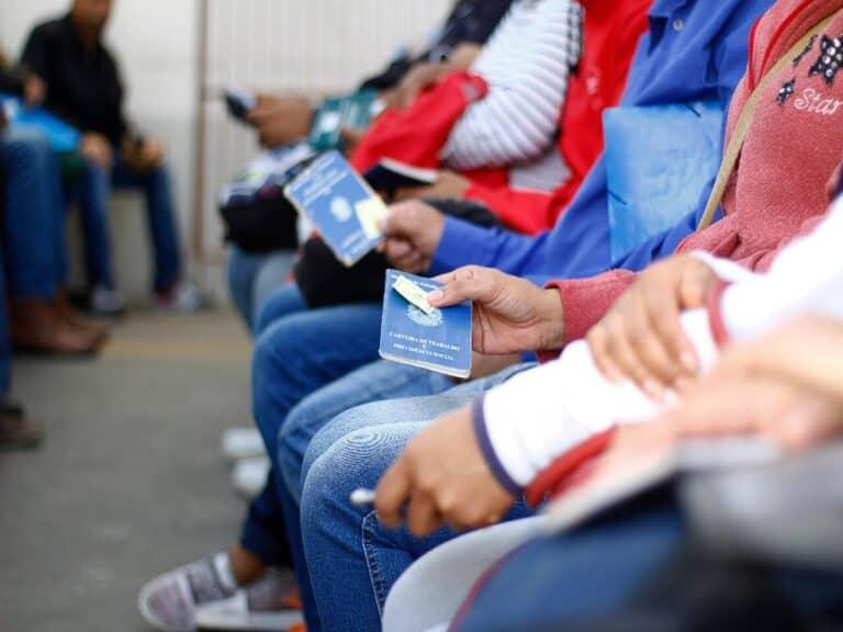 fila de pessoas sentadas segurando a carteira de trabalho na mão, representando taxa de desemprego
