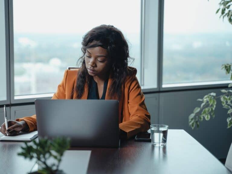 mulher utilizando computador, representando taxas para investir em renda variável