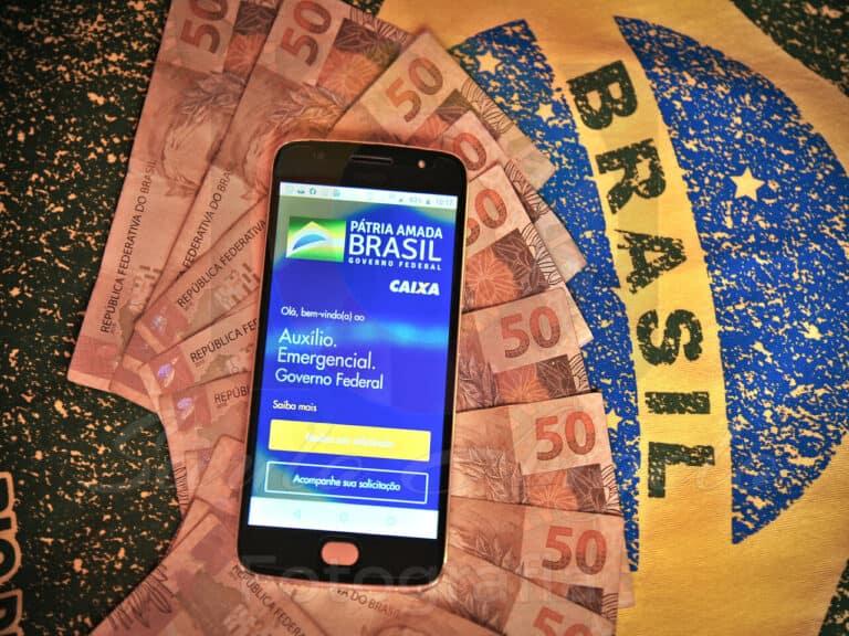 celular com a tela do auxílio emergencial em cima de várias notas de dinheiro e a bandeira do Brasil ao fundo