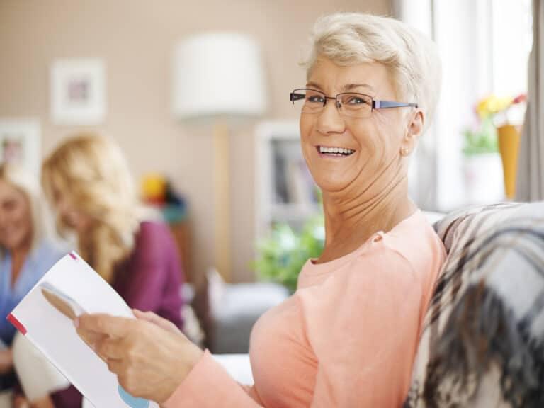 idosa sorrindo sentada de lado está com um folheto ou livro na mão, representando 13º salário dos aposentados 2021