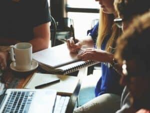 pessoas sentadas à mesa com notebook e caderno representando Balcão Único