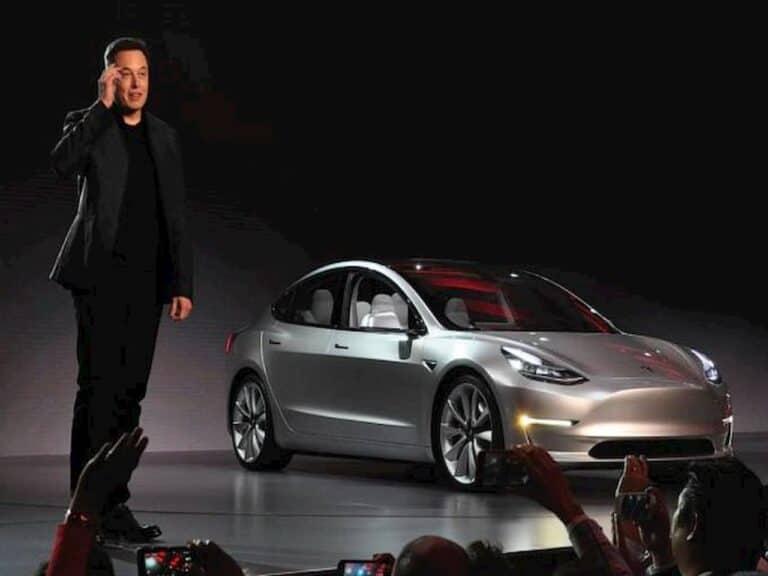 Elon Musk em pé em frente a um carro representando Musk supera Bezos