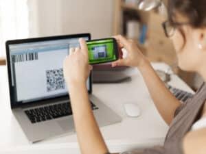 mulher está sentada na frente do computador e na tela tem um QR code. Ela segura um celular e está lendo o QR code da tela do computador, representando pagamento de conta de luz pelo pix