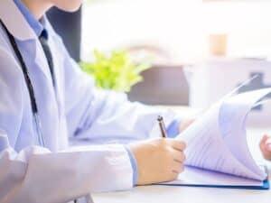 médico escrevendo, representando planos de saúde criam novos produtos