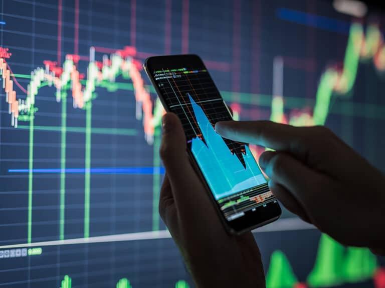 pessoa acessando gráfico de ações bancarias no celular