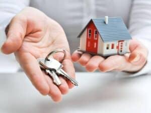 pessoa segurando um molho de chaves em uma mão e uma miniatura de casa em outra, simbolizando aluguel em 2021
