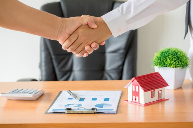 Duas pessoas apertam a mão em sinal de acordo. Em cima da mesa tem um contrato e uma miniatura de casa