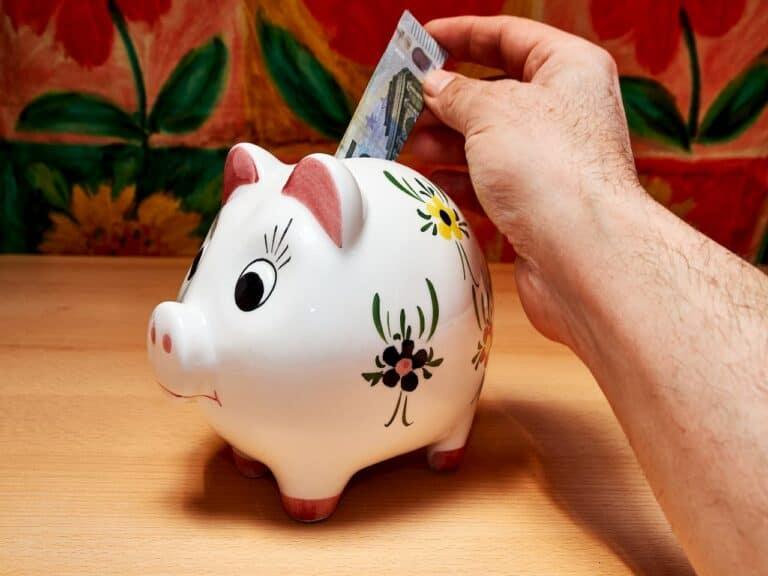 homem colocando cédula em porquinho representando caderneta de poupança