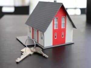 maquete de casa com chaves à frente representando carga tributária do Casa Verde e Amarela
