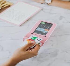 cartão visa sem anuidade sendo ilustrada por uma mão segurando um cartão da bandeira visa, com o fundo uma maquininha de cartão