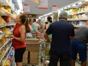 pessoas em supermercado comprando cesta básica
