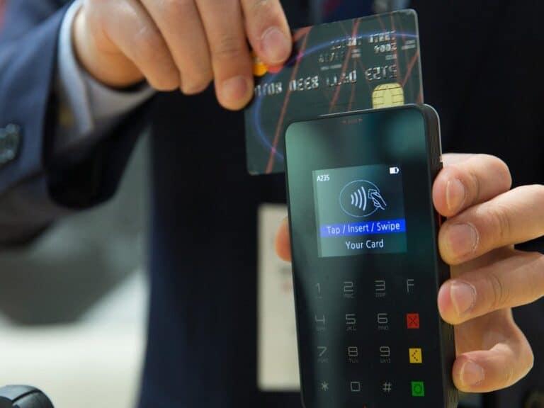 homem com uma maquinha de pagamentos portátil na mão e passando um cartão de crédito aguardando a resposta