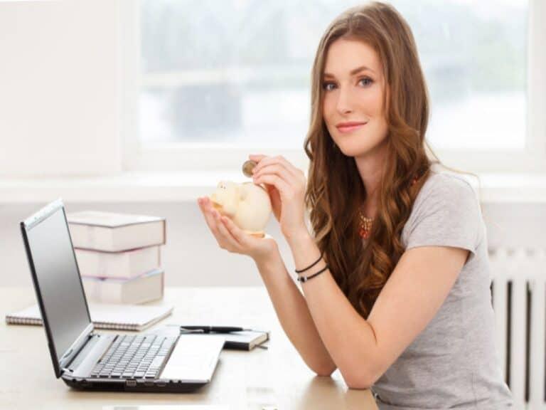 Mulher avalia como poupar dinheiro enquanto segura um cofrinho nas mãos