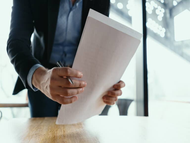 homem segura papéis na mão com uma caneta e vai colocá-los em uma mesa