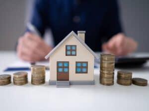 casa em minuatura com moedas, representando juros para crédito imobiliário