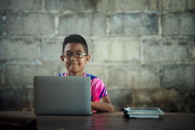 Criança usa computador para pesquisas e aulas online
