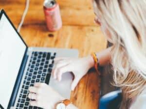 mulher loira estuda em frente a notebook