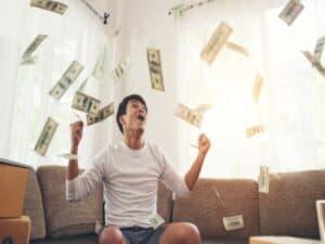 homem festeja com várias notas de dinheiro voando ao seu redor
