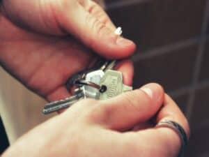 pessoa com chaveiro entre os dedos representando fundo para fiador de imóvel