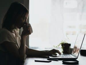 Imagem de uma mulher trabalhando em um computador, esse é um meio para ganhar dinheiro como afiliado