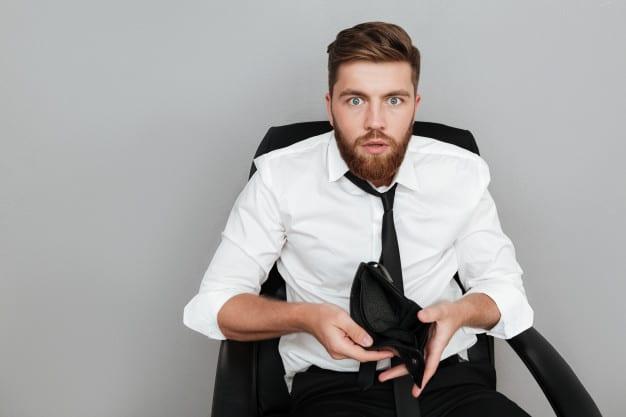 Rapaz com carteira vazia percebe que gastar excessivamente atrapalha seu planejamento financeiro pessoal