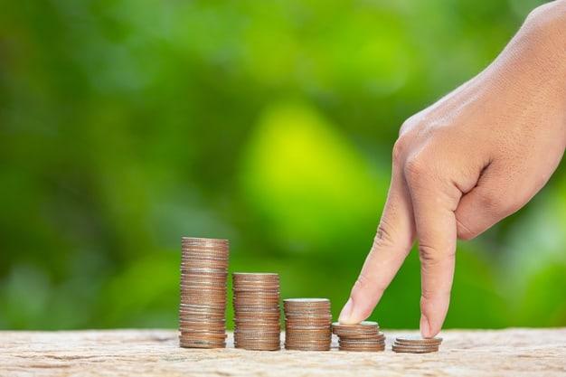mão sobe uma escada de moedas simbolizando o crescimento do conhecimento financeiro