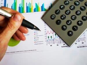 mão segurando caneta com calculadora e papéis com gráficos ao fundo representando impostos em dia na renda variável