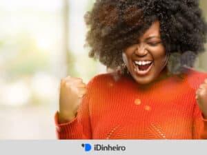 mulher comemorando pois aprendeu sobre investimentos para iniciantes