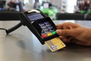 maquininha em loja com um cartão de crédito inserido uma pessoa apertando o botão verde para autorizar a operação