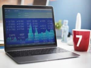 laptop mostra gráficos e números de operações de investimentos