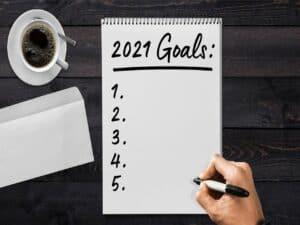 uma folha de caderno aparece escrito metas para 2021 e os números 1, 2, 3, 4 e 5 embaixo sem ter nada escrito ao lado Ainda tem a mão de um homem com uma caneta para escrever